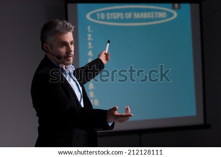 Cheerful trainer pointing at screen with presentation. Young businessman giving presentation and asking his colleagues - stock photo