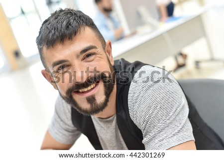 Cheerful trendy bearded guy in office