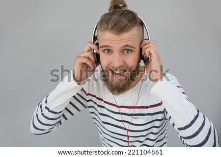 Cheerful trendy guy listening to music - stock photo