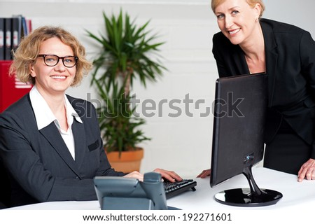 Cheerful two business women working at the office - stock photo