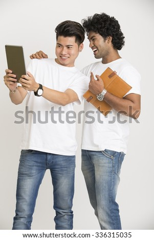 Cheerful two college students using digital tablet over white background - stock photo