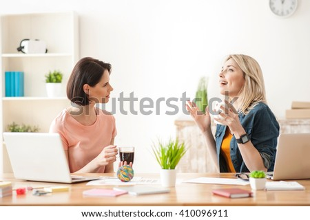 Cheerful two female colleagues are talking at work - stock photo