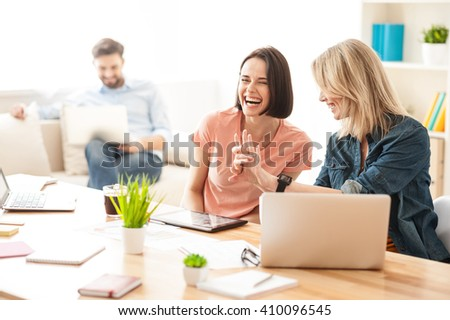 Cheerful two female workers are talking with joy - stock photo