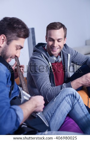 Cheerful two friends are entertaining with musical instrument