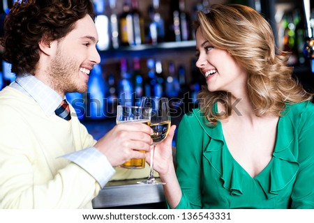 Cheerful two friends celebrating their weekend while drinking in a bar. - stock photo