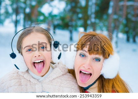 cheerful two girls in the winter forest, two funny portrait in winter, - stock photo