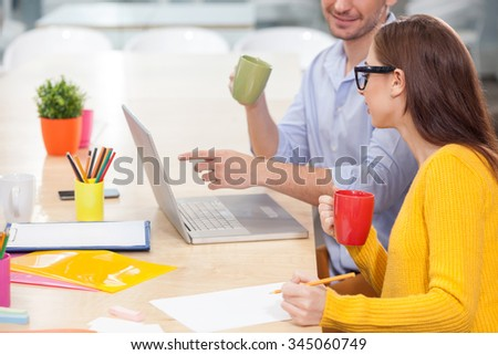 Cheerful two workers are discussing new project. They are sitting at the desk and smiling. The man is using a laptop. The woman is writing and drinking coffee - stock photo