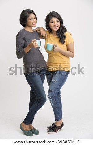 Cheerful two young female friends standing with coffee cups on white background. - stock photo