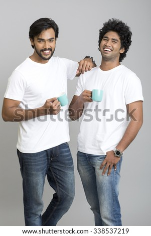 Cheerful two young men chatting with coffee cup on grey background.