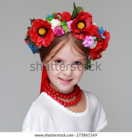 Cheerful Ukrainian smiling little girl with a wreath on head - stock photo