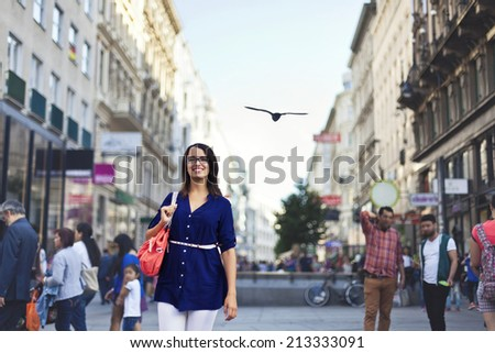 Cheerful urban girl standing out from the crowd at a city street. - stock photo