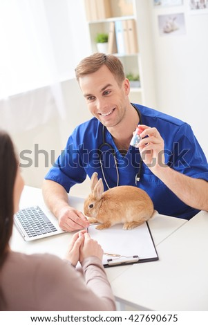 Cheerful vet is advising medication for pet - stock photo