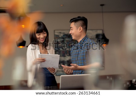 Cheerful Vietnamese couple discussing business idea