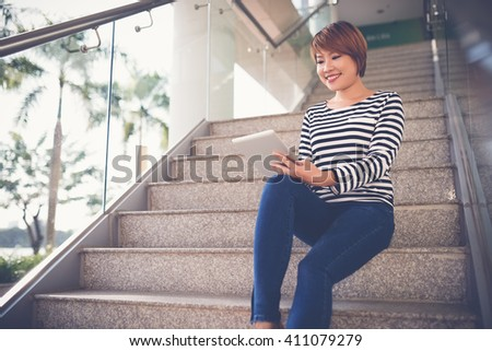 Cheerful Vietnamese girl with tablet computer sitting on the steps - stock photo