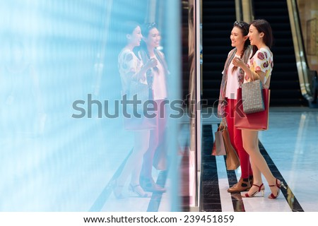 Cheerful Vietnamese girls looking at the showcase in the mall - stock photo