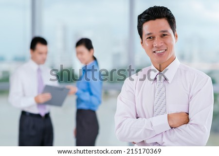Cheerful Vietnamese manager looking at the camera while his colleagues talking in background - stock photo