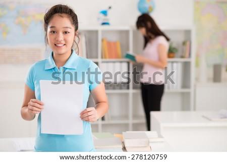 Cheerful Vietnamese schoolgirl holding blank sheet of paper - stock photo