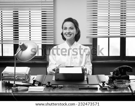 Cheerful vintage secretary working at office desk and smiling at camera - stock photo