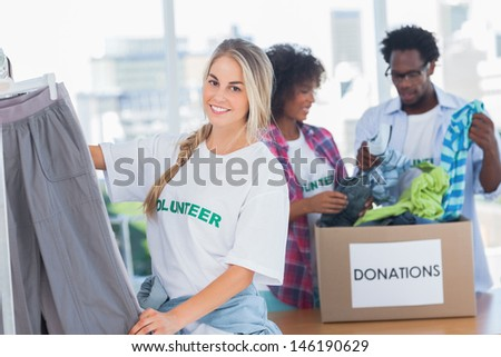Cheerful volunteers putting clothes in clothes rail in their office - stock photo