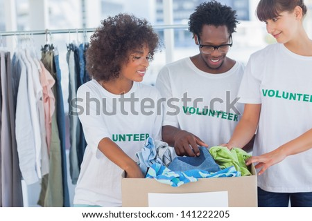 Cheerful volunteers taking out clothes from a donation box in their office - stock photo