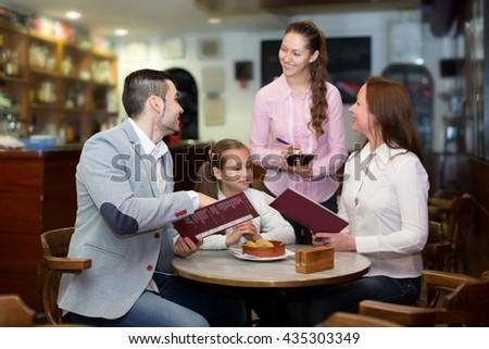 Cheerful waitress and smiling family with child reading menu. Focus on the man - stock photo