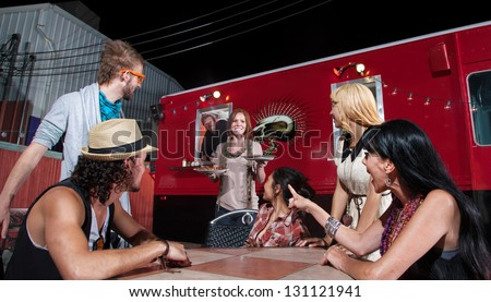 Cheerful waitress bringing orders to people at pizza truck - stock photo