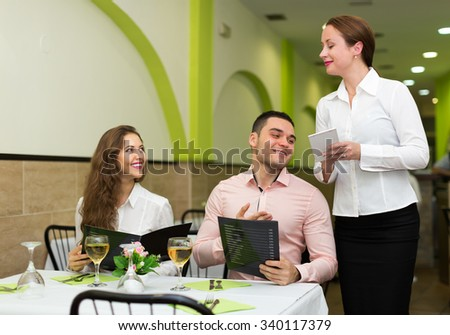 Cheerful waitress offering to young couple tasty dishes - stock photo