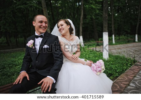 Cheerful wedding couple sitting on bench leaning backs to each other - stock photo