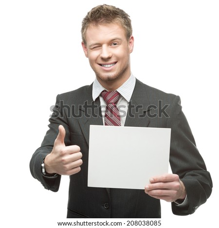 cheerful winking caucasian businessman in gray suit holding sign and showing thumb-up isolated on white background - stock photo