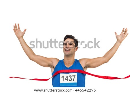 Cheerful winner athlete crossing finish line with arms raised on white background - stock photo