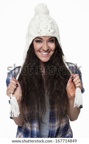 Cheerful winter portrait of a young woman in a cap and plaid shirt. Isolated on white background. - stock photo