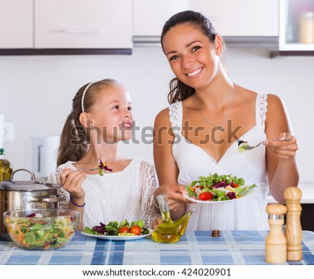 Cheerful woman and little girl holding plates with salad in kitchen - stock photo