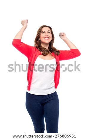Cheerful woman celebrating with arms up.