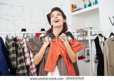 Cheerful woman choosing dress in store  - stock photo
