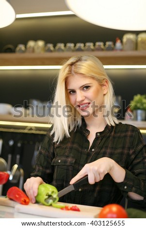 Cheerful woman cooking vegetable salad at home and looking at camera.  - stock photo