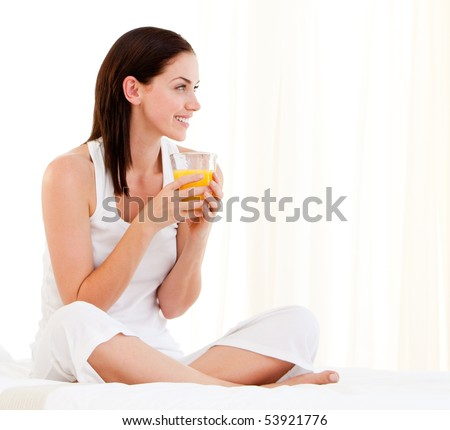 Cheerful woman drinking an orange juice sitting on her bed at home - stock photo