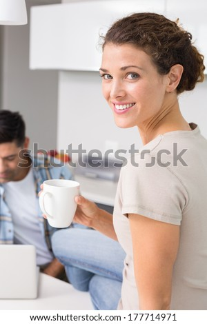 Cheerful woman drinking coffee while partners uses laptop at home in kitchen - stock photo