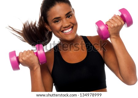 Cheerful woman exercising and building up biceps using dumbbells. - stock photo