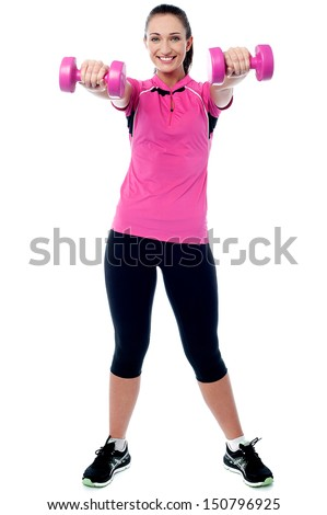 Cheerful woman exercising with pink dumbbells