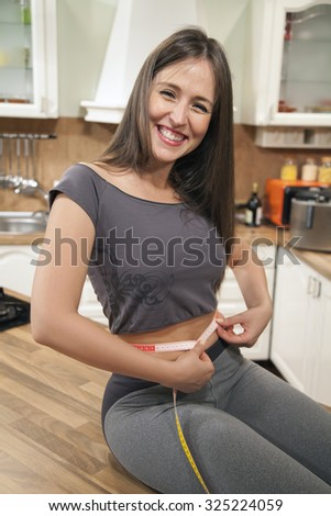 Cheerful woman feeling happy about her weight loss. She is measuring her slim waist with tape measure after dieting while sitting on kitchen counter and looking at camera. - stock photo