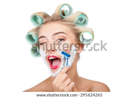 Cheerful woman has having cream over her face. She is shaving herself with razor. The girl is winking and laughing. Isolated on background and copy space in right side - stock photo