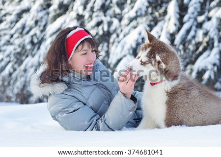 Cheerful woman having fun with her little cute Siberian Husky puppy in winter forest full of snow. Lifestyle concept.  - stock photo