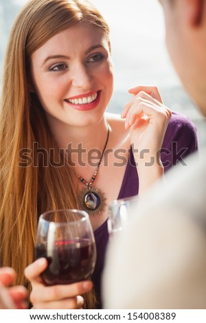 Cheerful woman having glass of wine with her boyfriend in bright terrace - stock photo
