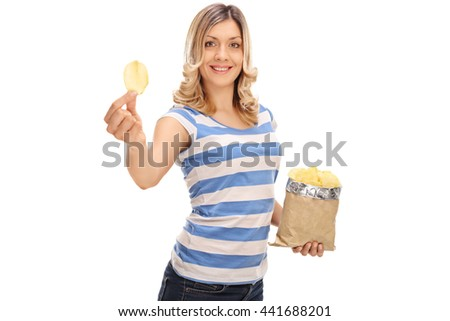 Cheerful woman holding a bag of potato chips in one hand and a single chip in the other isolated on white background - stock photo
