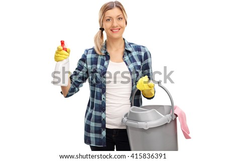Cheerful woman holding a cleaning spray and a plastic bucker isolated on white background - stock photo