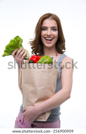 Cheerful woman holding a shopping bag full of groceries - stock photo