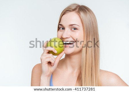 Cheerful woman holding apple and looking at camera isolated on a white background - stock photo
