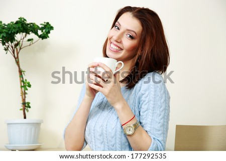Cheerful woman holding cup with coffee at home - stock photo