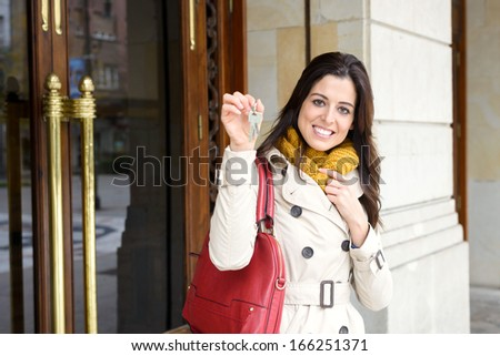 Cheerful woman holding home keys at apartment building entrance door outside. Happy and tranquil ownership, household insurance or rental concept. - stock photo