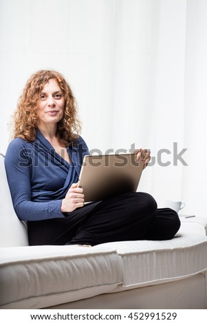 Cheerful woman in blue blouse and curly locks of red hair sitting on white sofa with tablet in hand